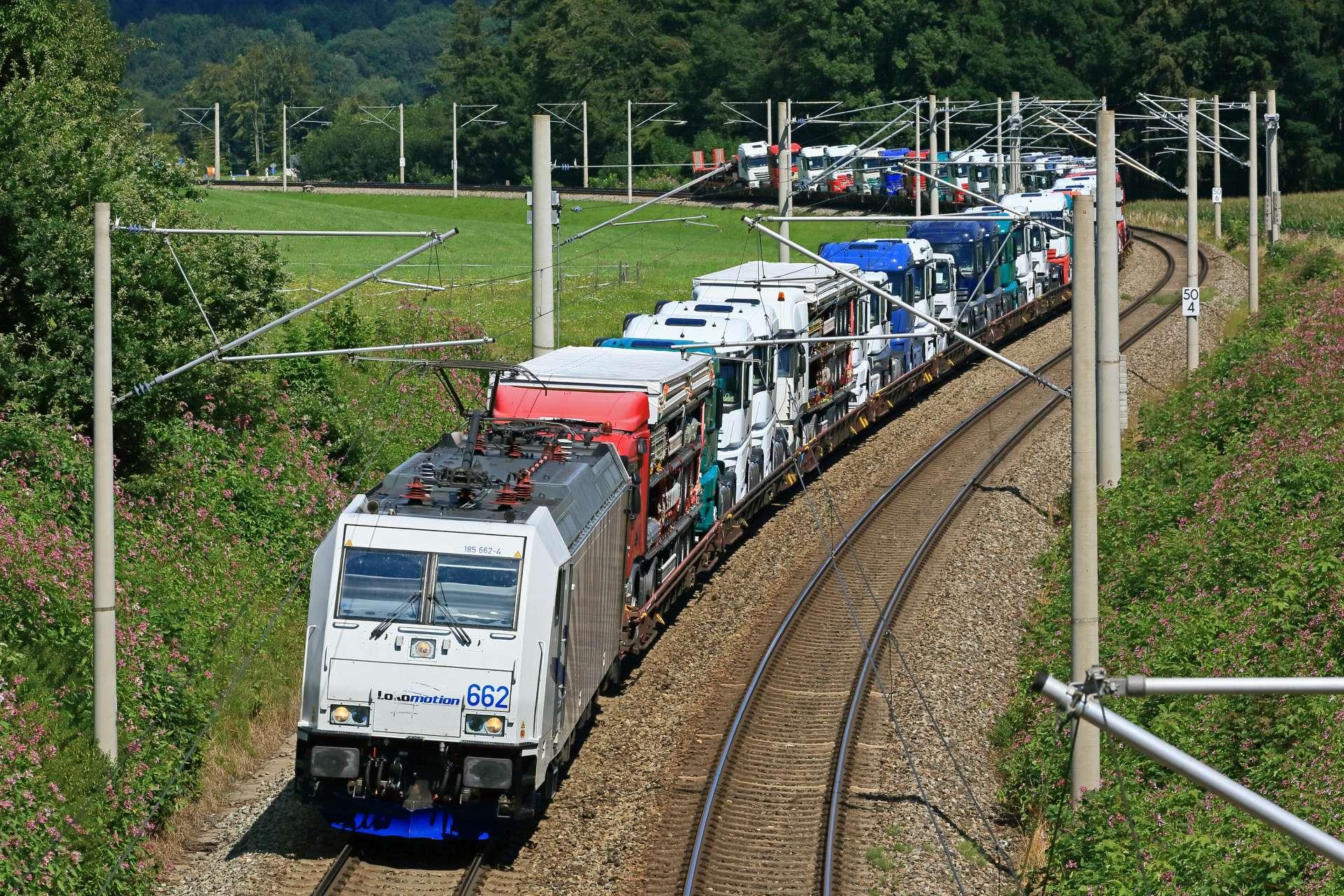<p>Eine Ellok der Baureihe 185 des EVU Lokomotion GmbH  durchfährt mit einem Zug voller fabrikneuer Mercedes-Lkw zwischen  Traunstein und Bergen (Obb.) den kurvigen Streckenabschnitt bei  Axorf.</p>